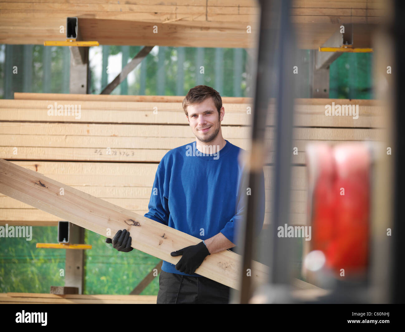 Worker holding planks of wood in joinery - Stock Image