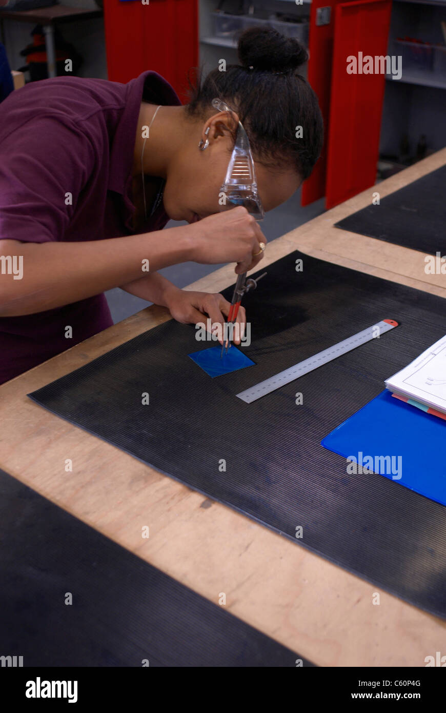 Worker tracing with compass in factory - Stock Image
