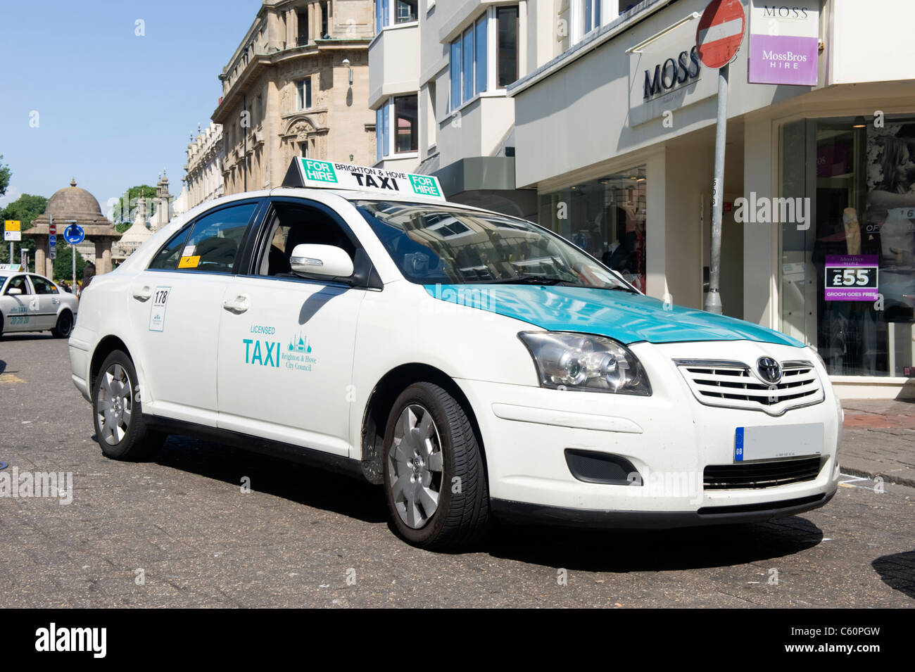 Brighton East Sussex typical licensed Toyota taxi cab in turquoise white livery waiting for custom passengers shop - Stock Image