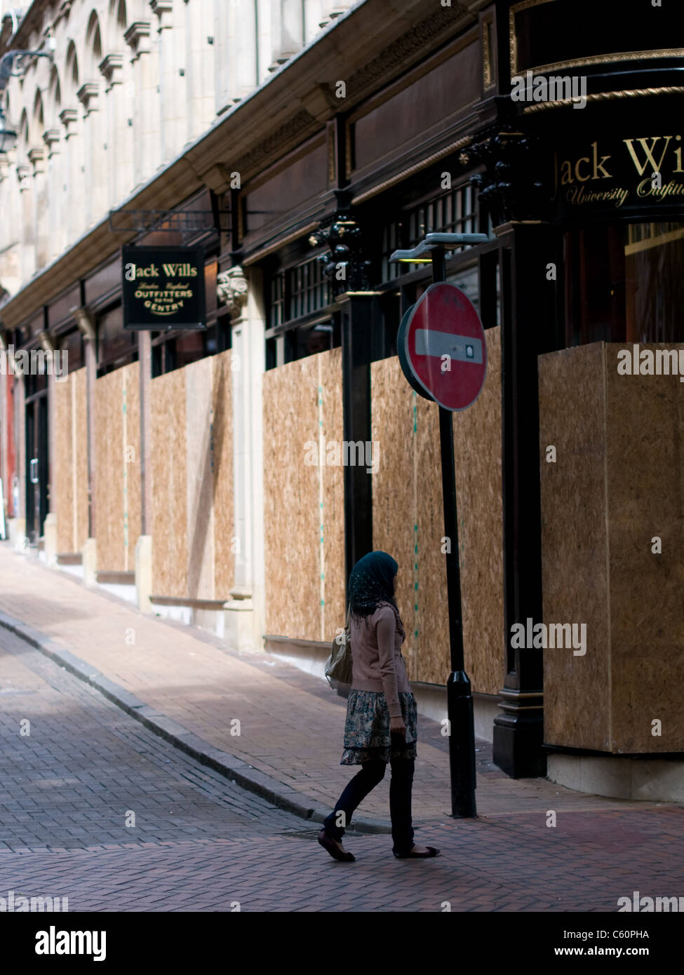 Young Muslim woman walks past a boarded-up Jack Wills store on New Street Birmingham following the riots of 2011. - Stock Image