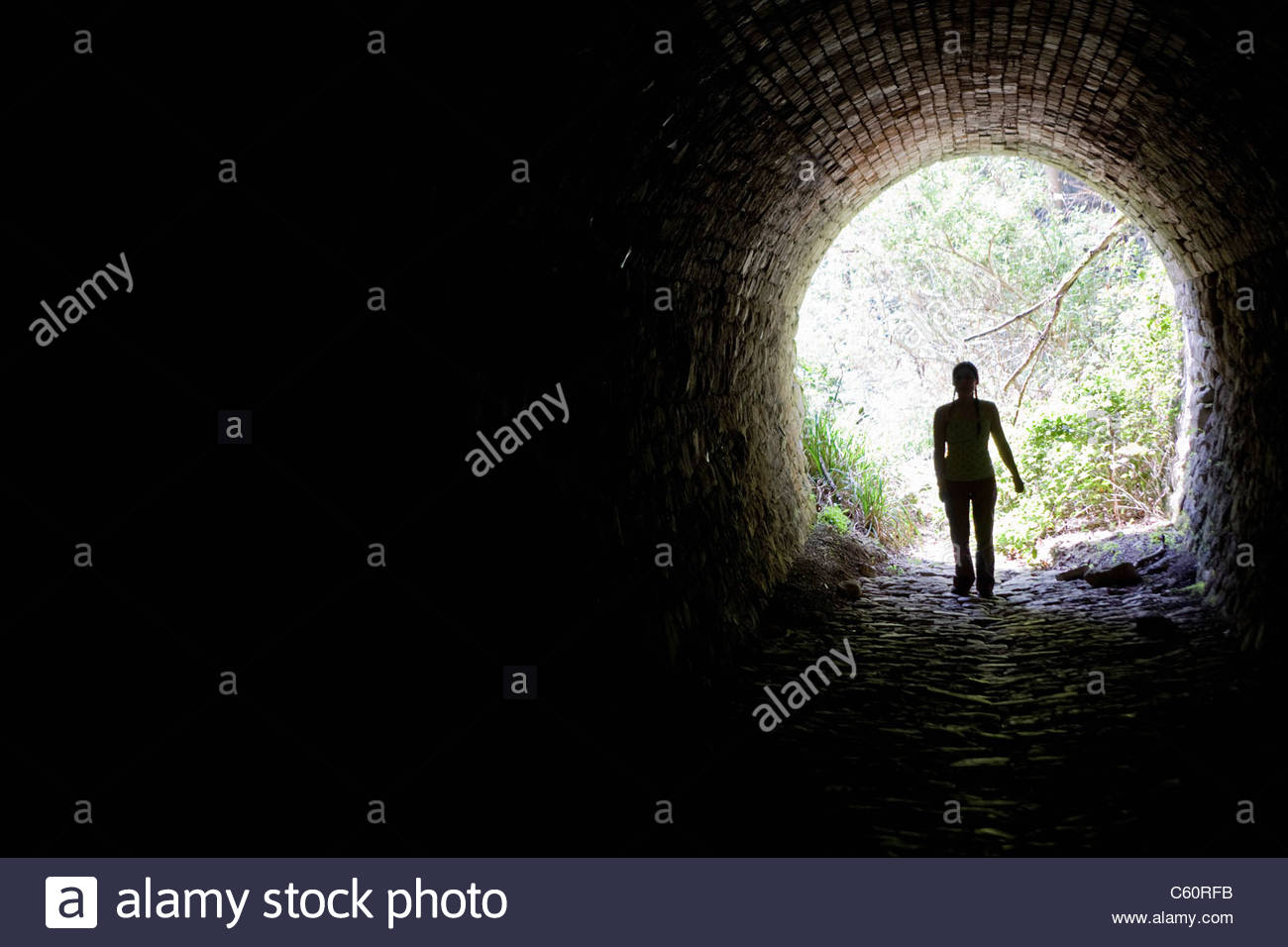 Woman walking in tunnel - Stock Image