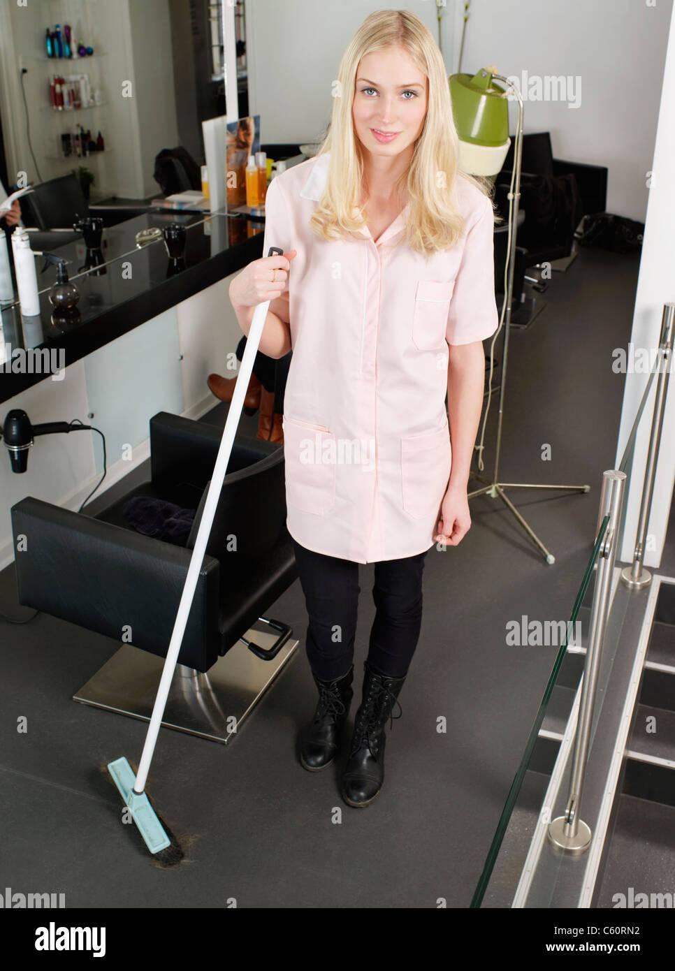 Hairdresser holding broom in salon - Stock Image