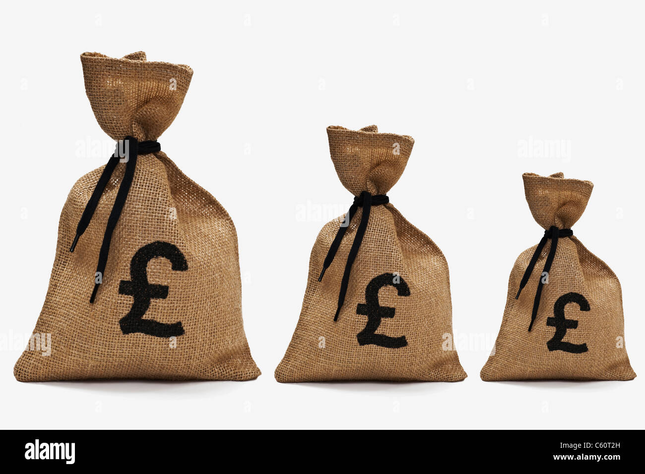 three different big money bags with pound sign next to each other - Stock Image