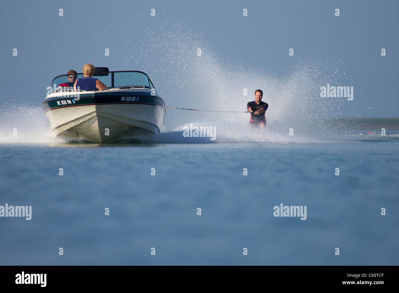 An approaching boat pulling a barefoot waterskier. - Stock Image