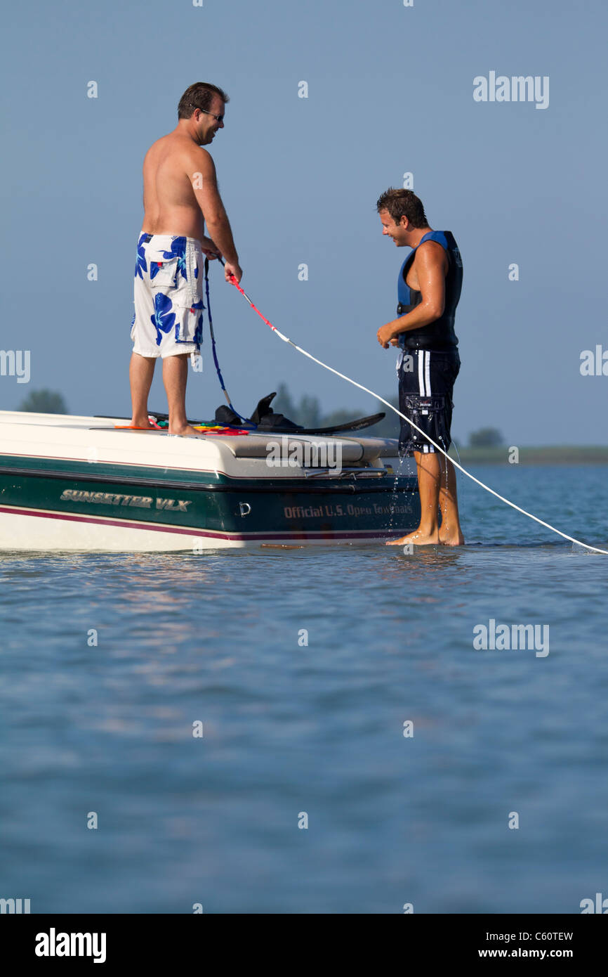 Two men on the back of a boat getting ready to waterski. - Stock Image