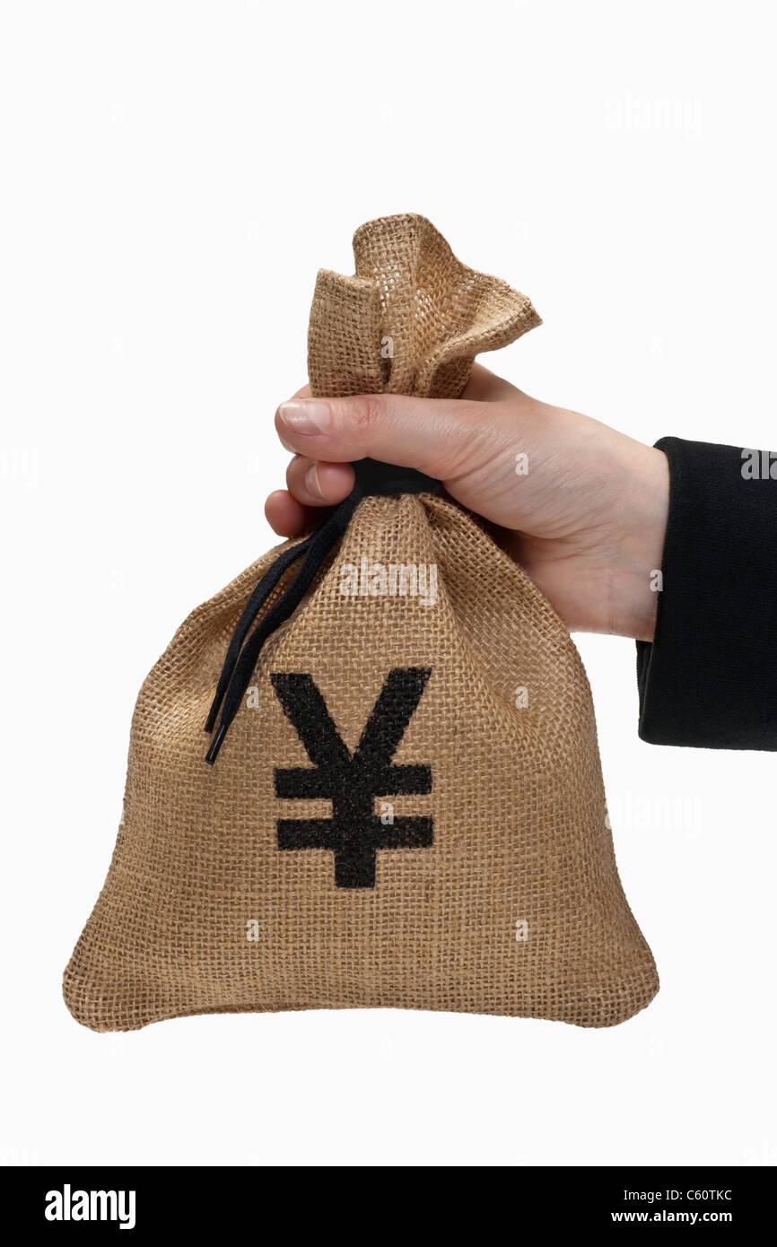 ein Geldsack mit Yen-Symbol wird in der Hand gehalten | a money bag with yen sign is hand-held - Stock Image