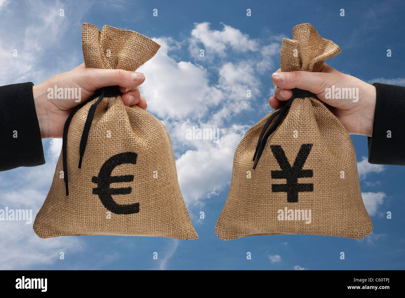 a money bag with euro sign and a money bag with yen sign are hand-held - Stock Image
