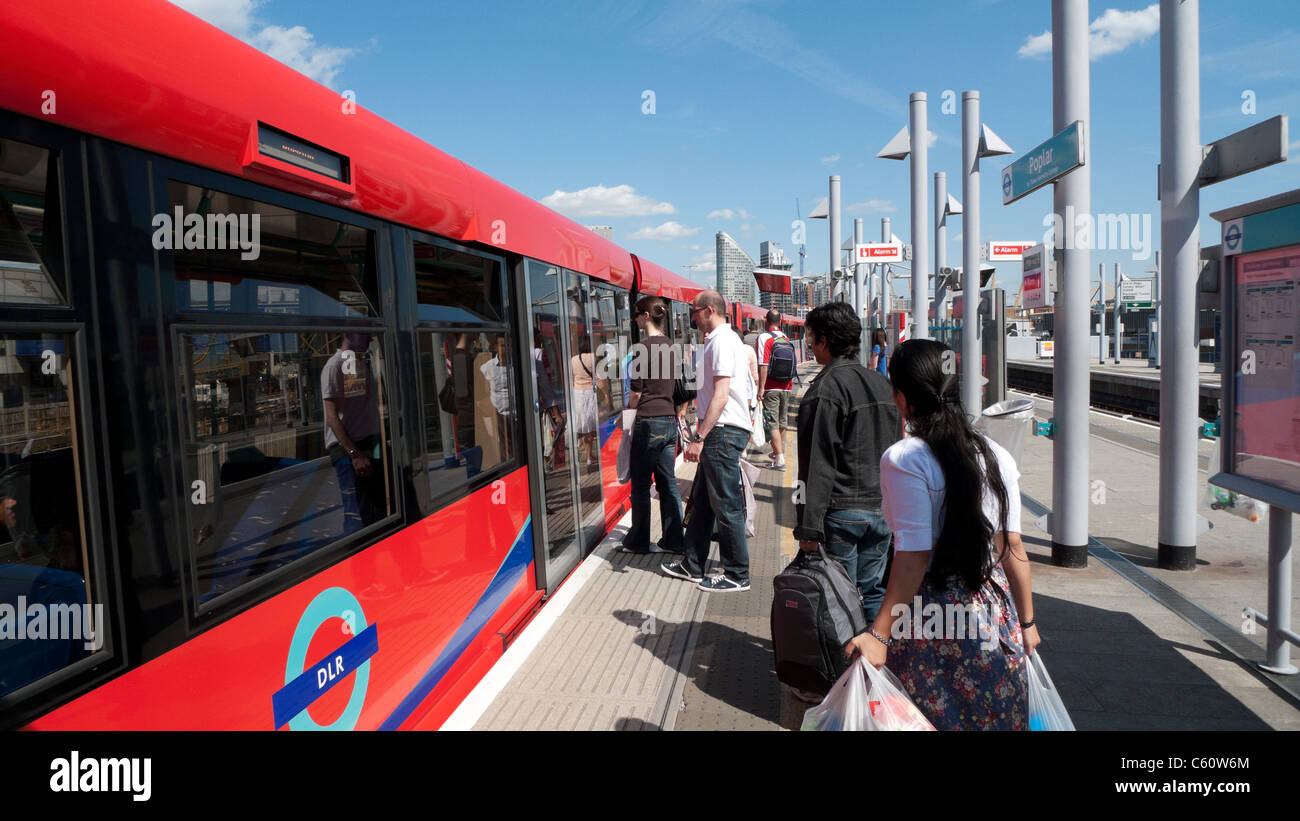 Passengers boarding a DLR Docklands Light Railway train carriage at Poplar, East London UK - Stock Image