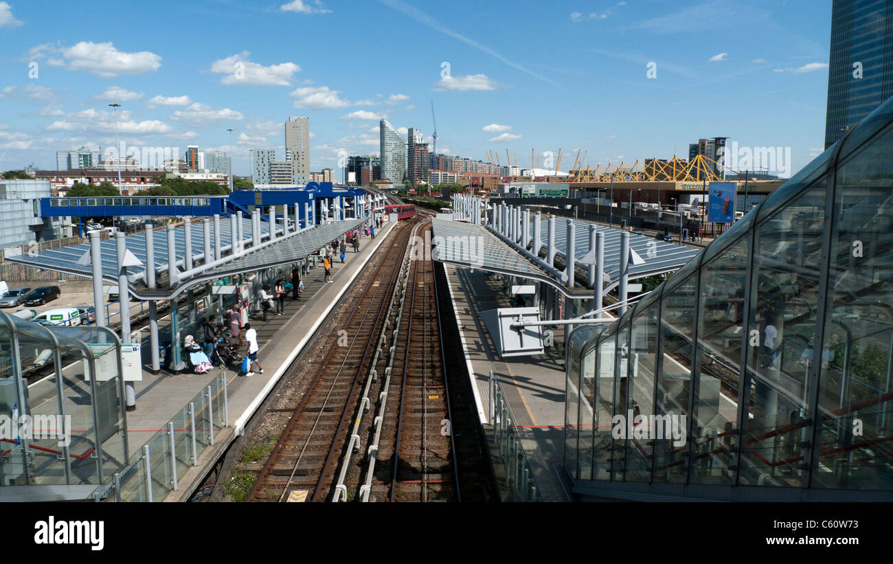 A view looking east of empty rail tracks with passengers waiting for the DLR train at Poplar Station East London - Stock Image