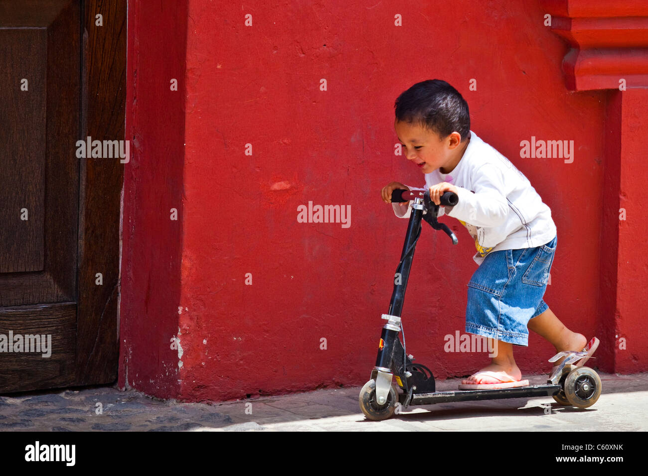 Young boy playing on a razor scooter, Antigua, Guatemala - Stock Image