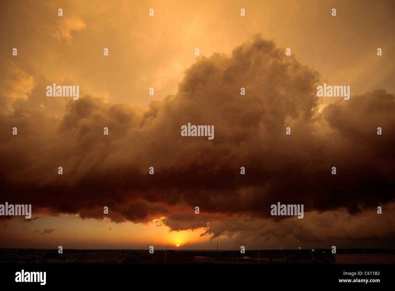 Detail of the setting sun illuminating the underside of a squall line. Stock Photo