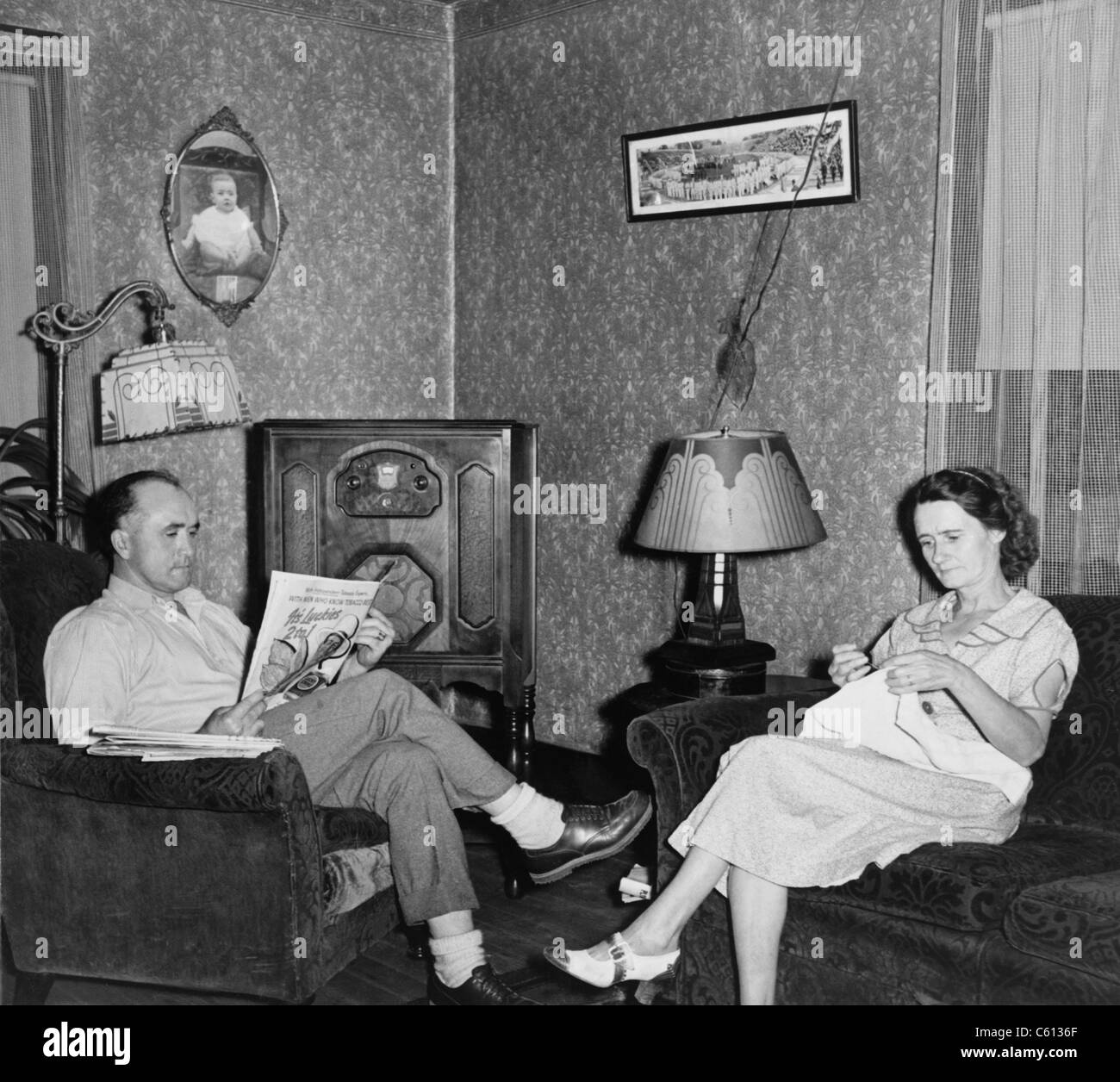 The comfortable living room of the home of a West Virginia coal miner and his wife, features a radio and electric - Stock Image