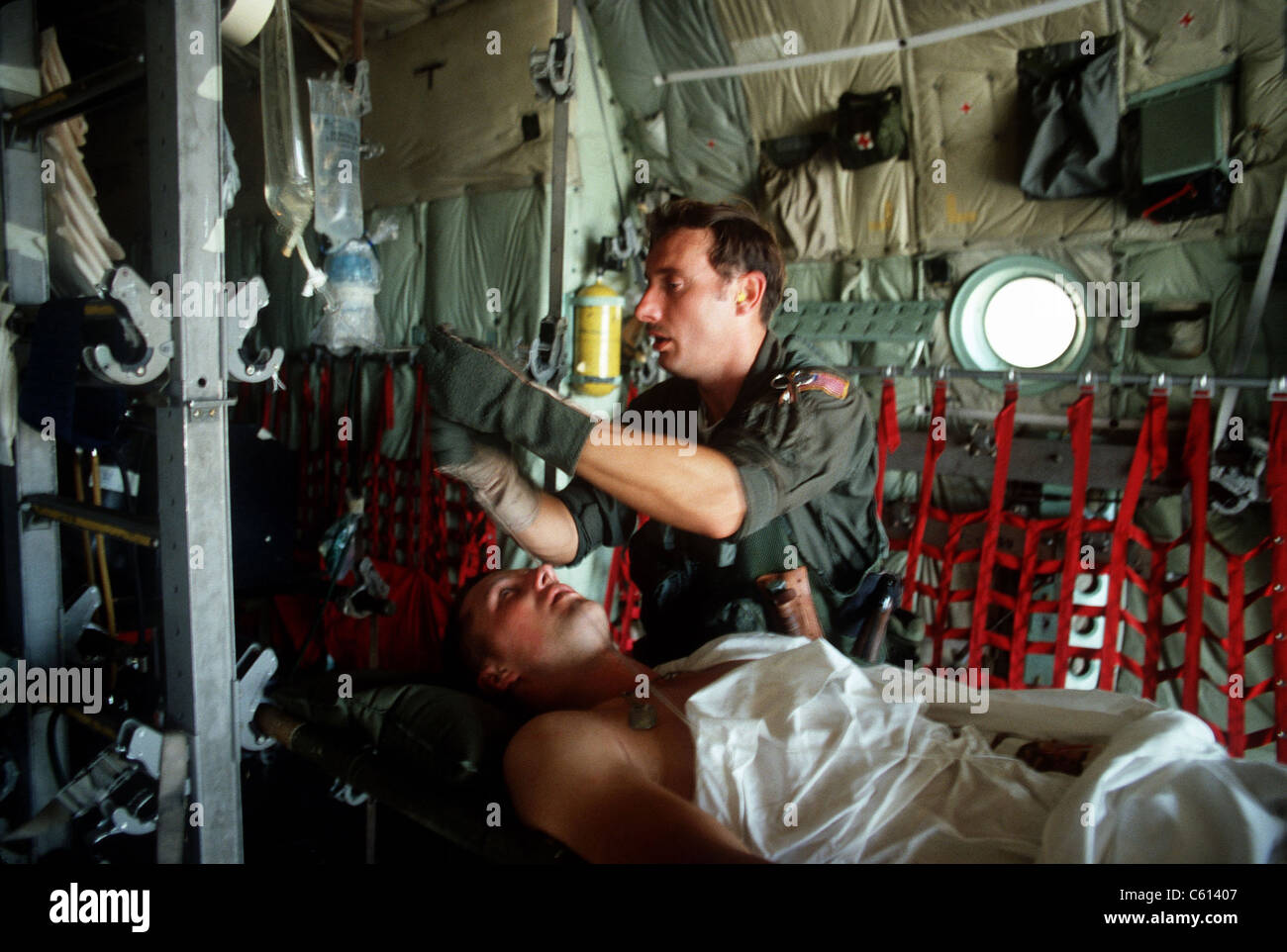 A medic adjusts the intravenous drip bag of a wounded US serviceman en route to a medical facility after the invasion - Stock Image