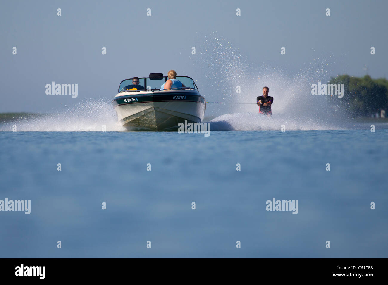 A fast approaching ski boat pulling a barefoot waterskier. - Stock Image