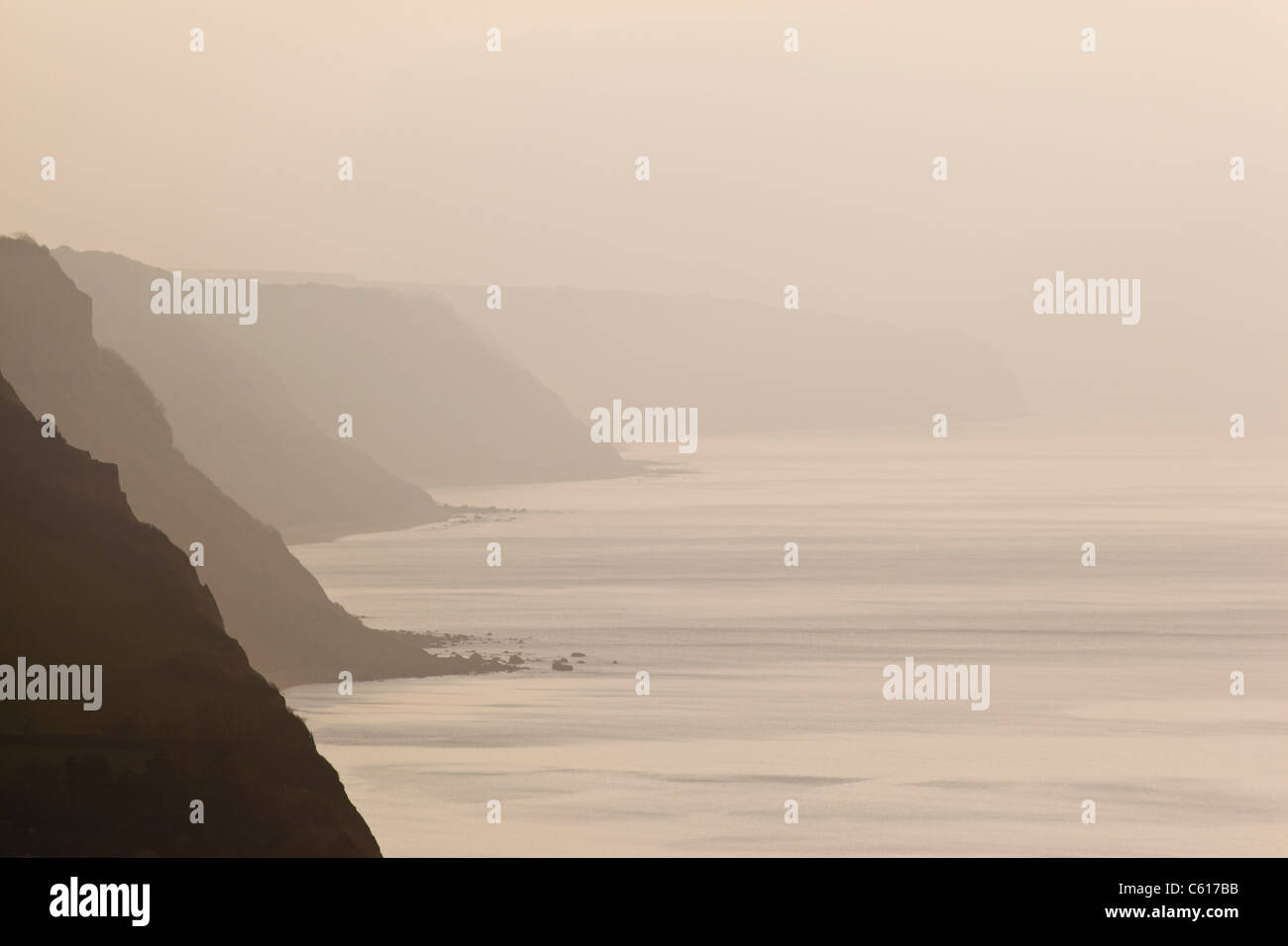 Sea mist obscuring distant silhouetted cliffs - Stock Image