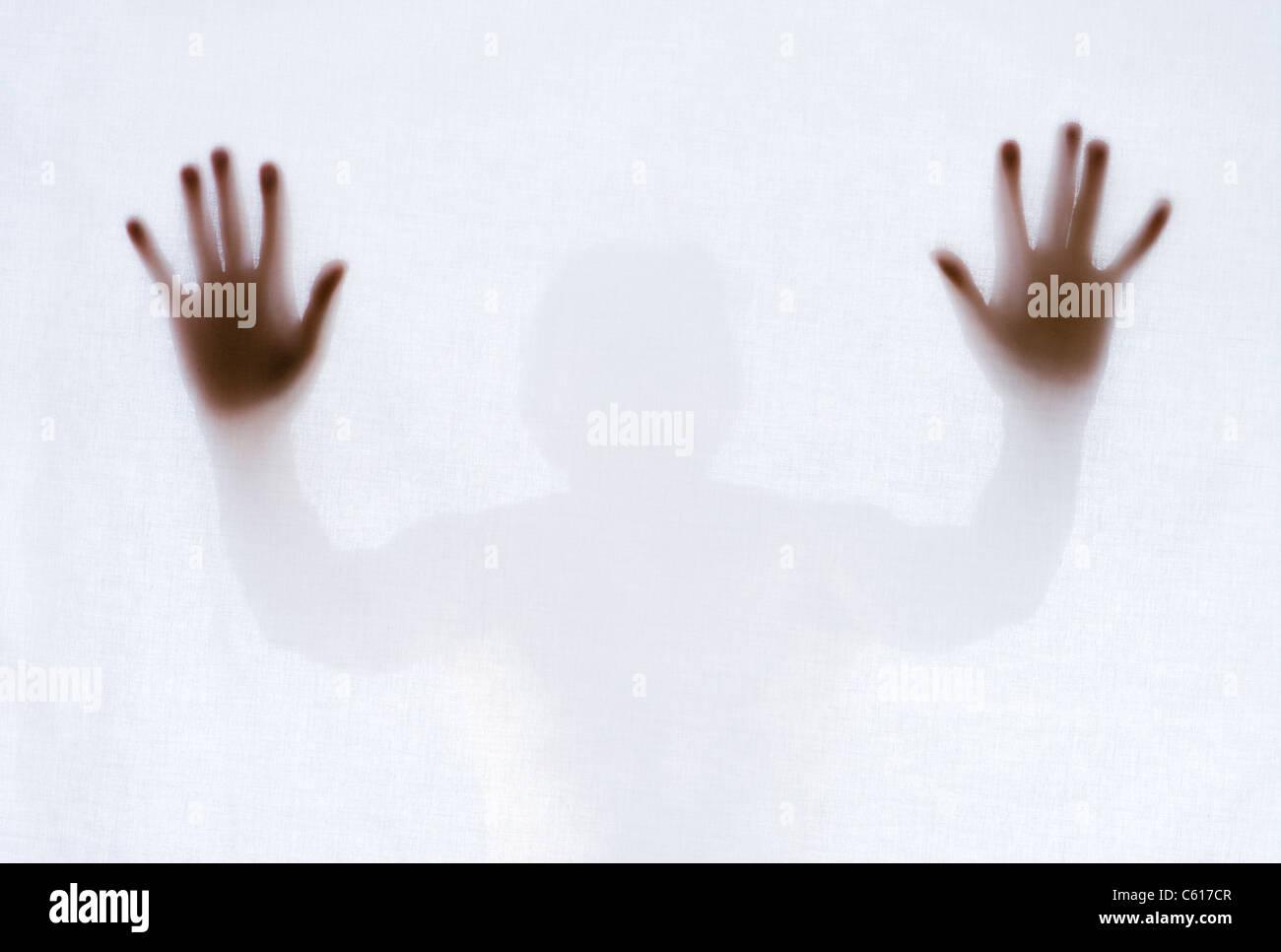 Silhouette of man behind sheet. - Stock Image
