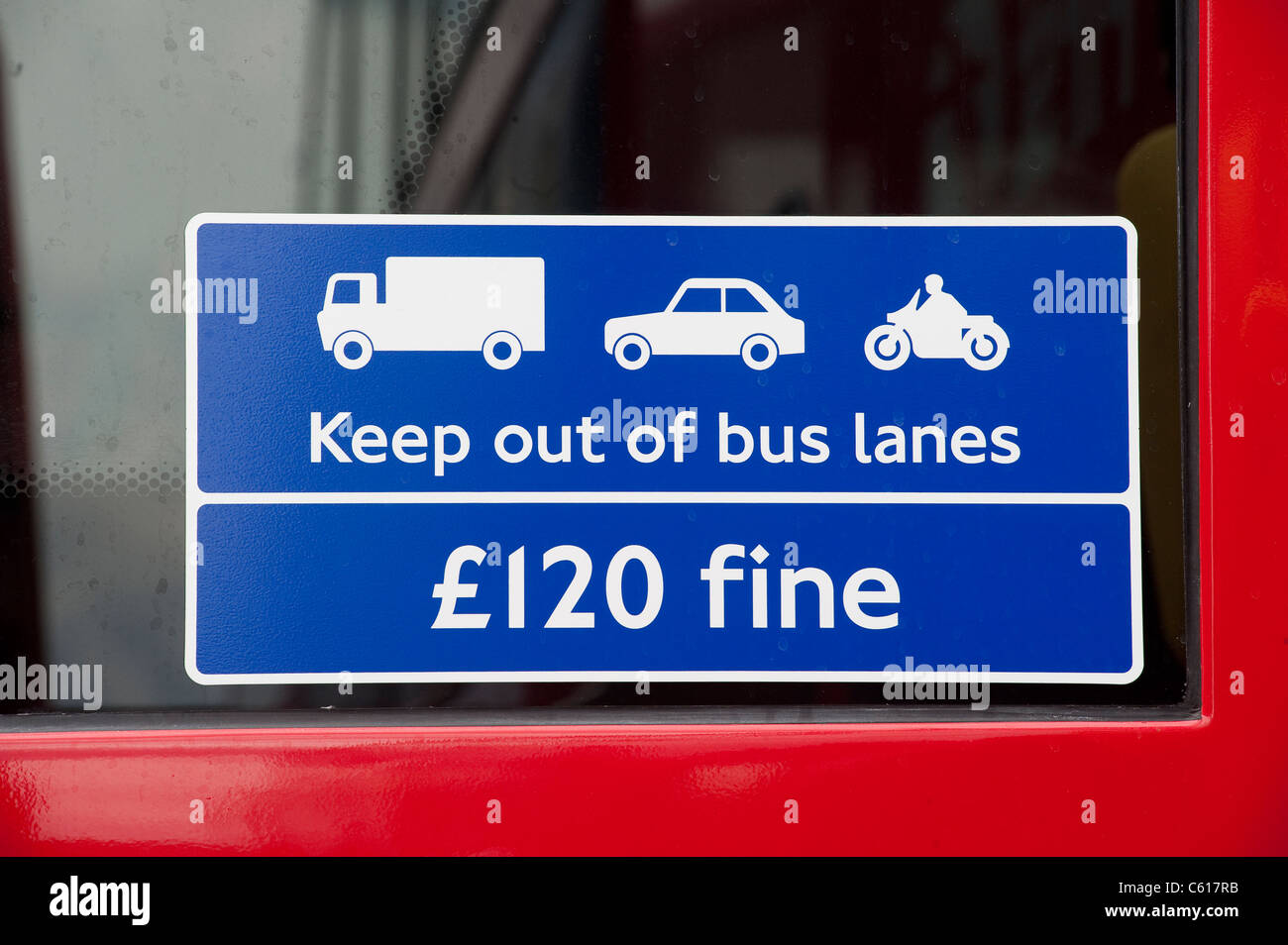 Sign in a bus window warning other traffic to stay out of bus lanes or face a fine. - Stock Image