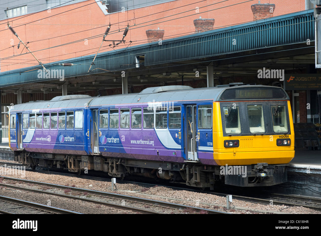 Class 142 train in Northern Rail livery waiting at a railway station in England. - Stock Image
