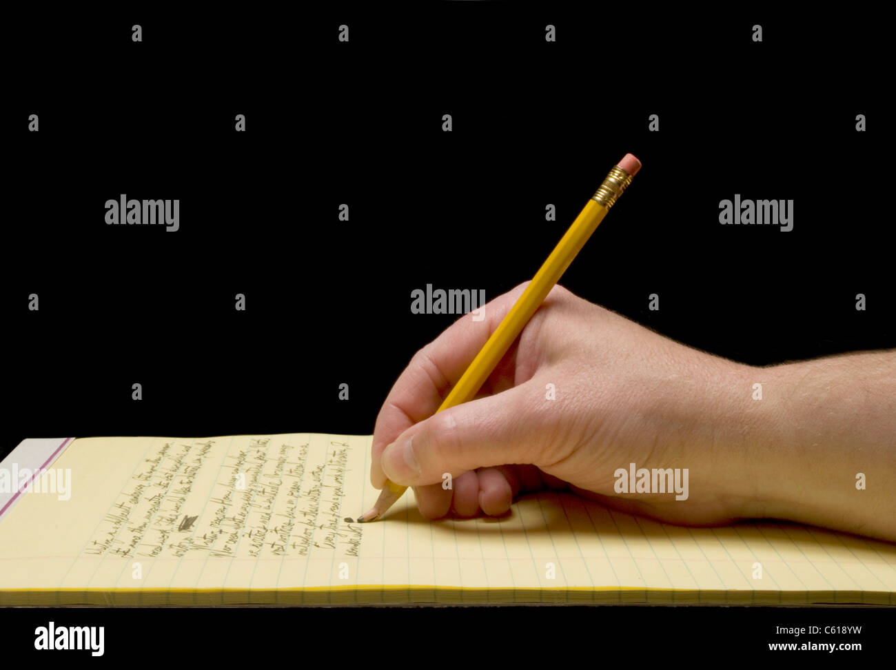 Handwriting with broken pencil point on yellow legal pad - Stock Image