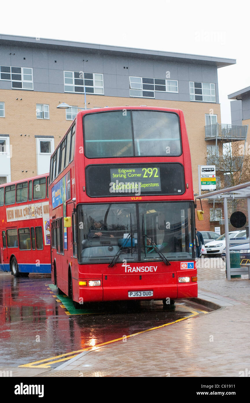 Red double decker bus in Transdev livery waiting at a bus stop. - Stock Image