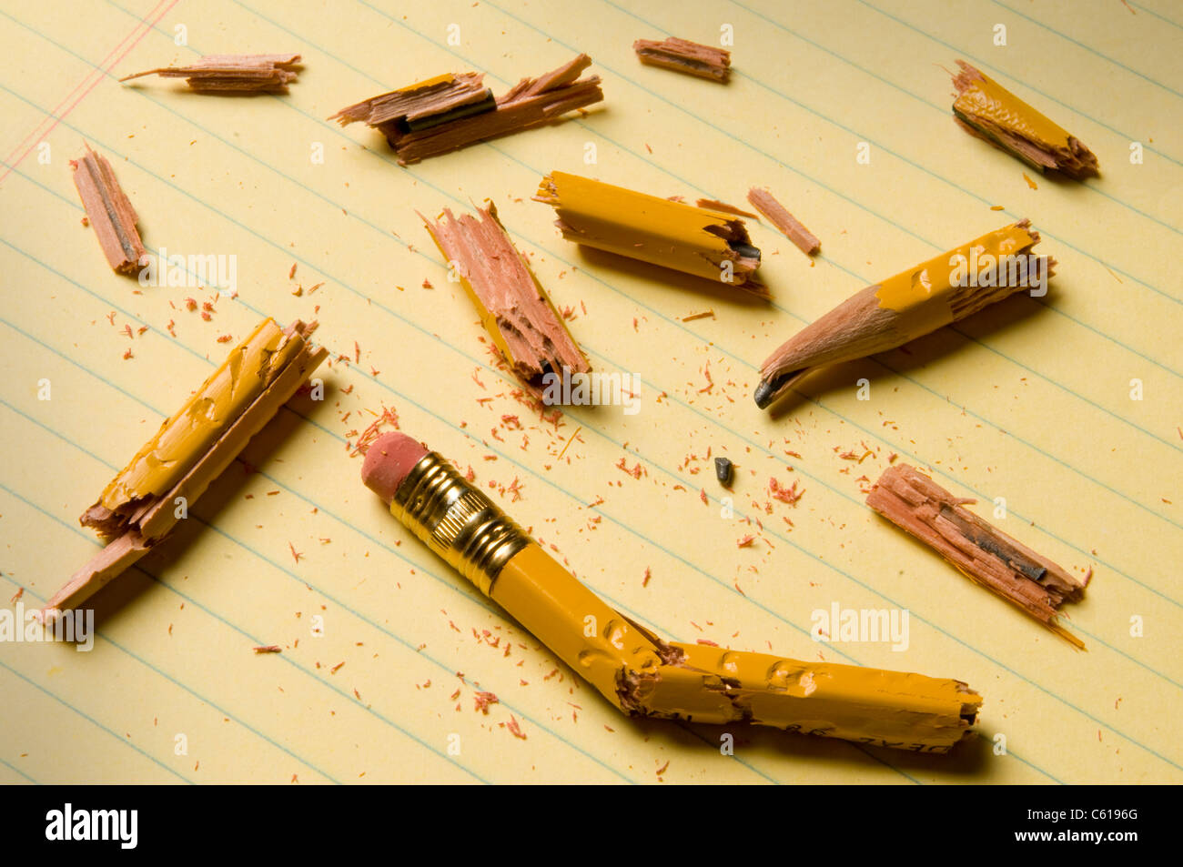 Shattered pencil fragments on a yellow legal pad, perhaps symbolizing writer's block - Stock Image