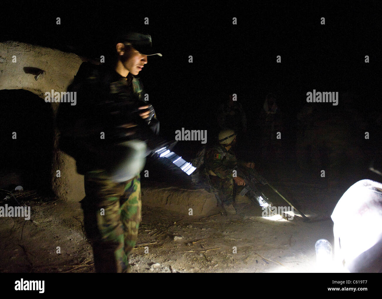 An Afghan national army commando assisted by U.S. Army Special Forces and Navy SEALs with Special Operations Task - Stock Image