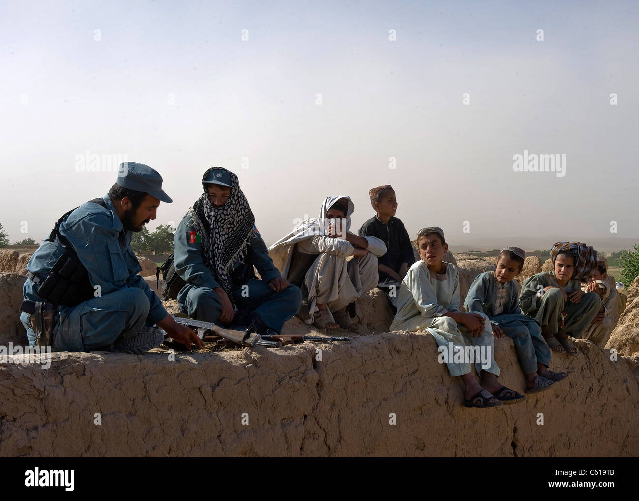 Members of the Afghan national police speak with Afghan children during a clearing operation in Khakrez district, Stock Photo