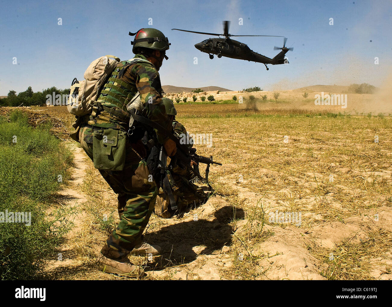 An Afghan commando braces himself as a UH-60 Black Hawk helicopter comes in to extract him following a clearing - Stock Image