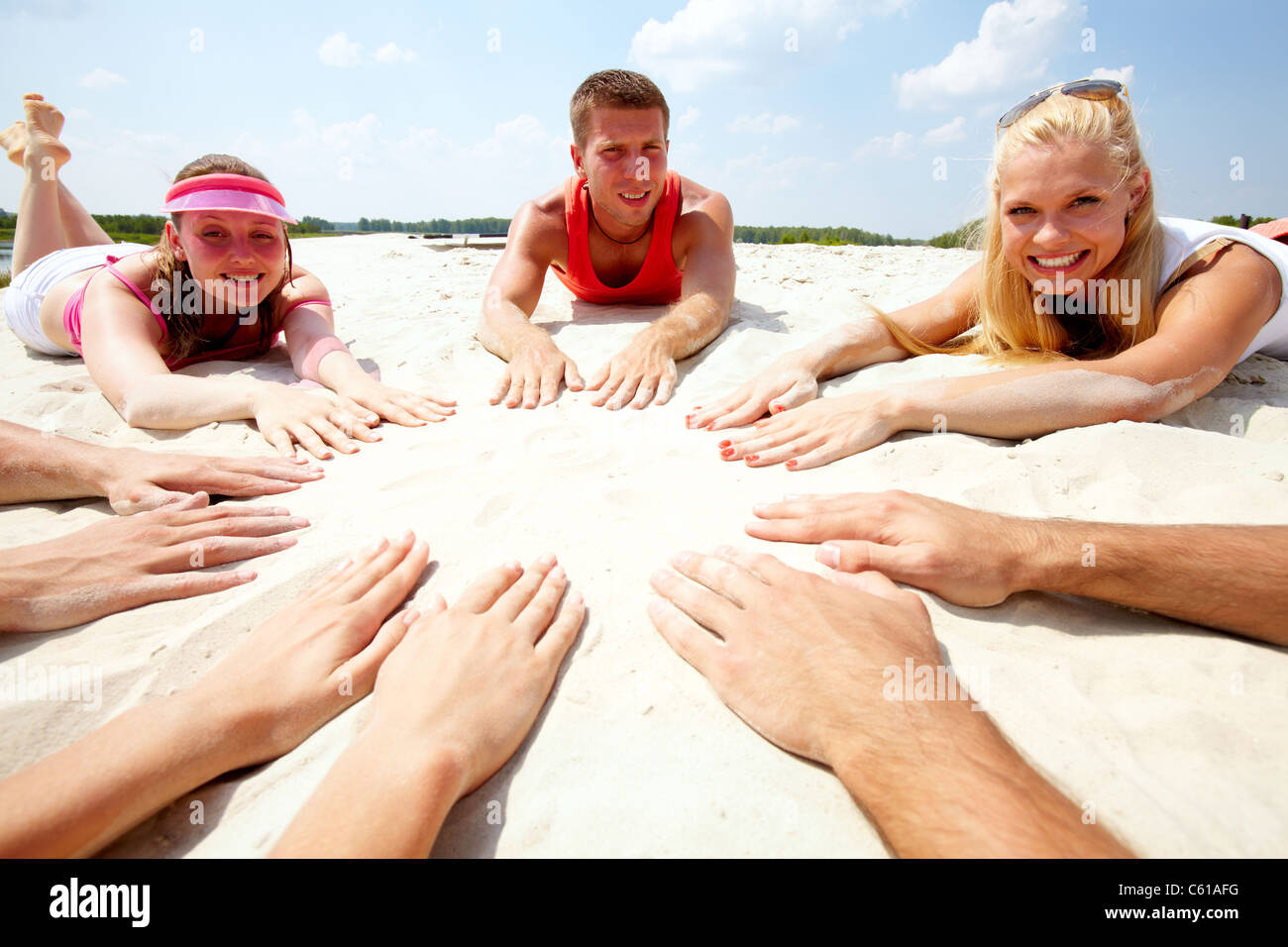 Image of several teens lying on beach and keeping their hands on sand in the form of circle - Stock Image