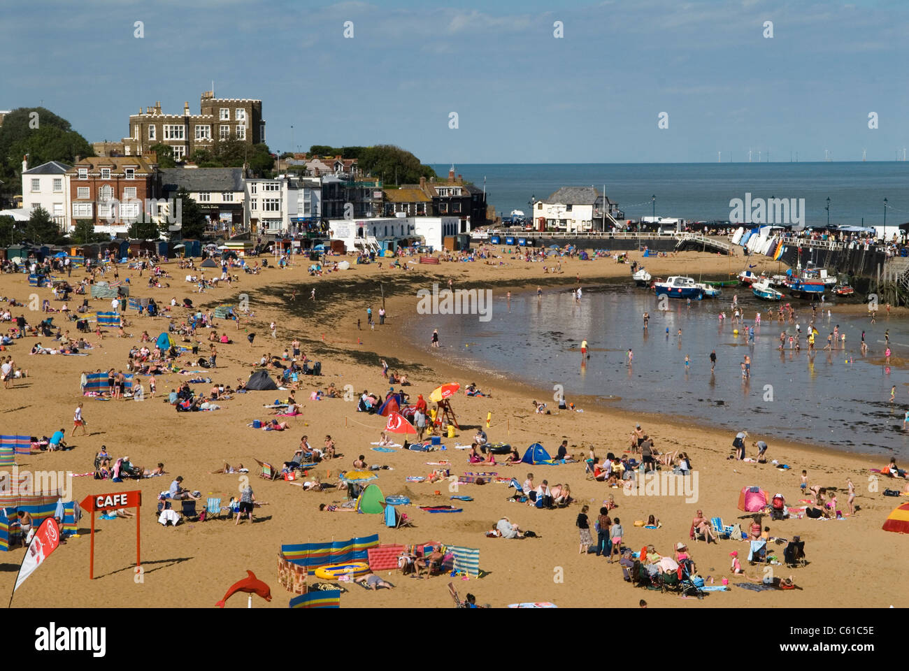 Broadstairs Kent Uk. Viking bay beach tourists on their annual summer holidays. Bleak House over looking the bay. - Stock Image