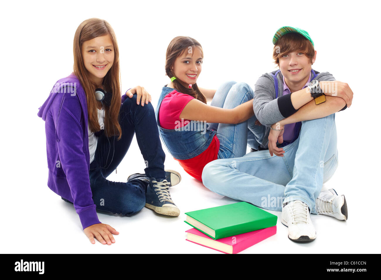 Three teenagers in casual clothes sitting in isolation - Stock Image