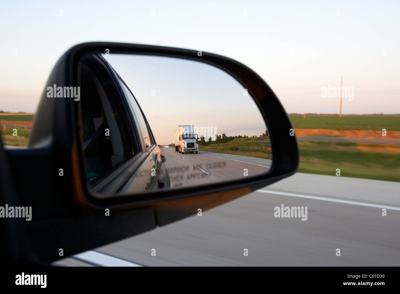 car wing side mirror showing rear view and semi truck while driving along a highway in the usa Stock Photo