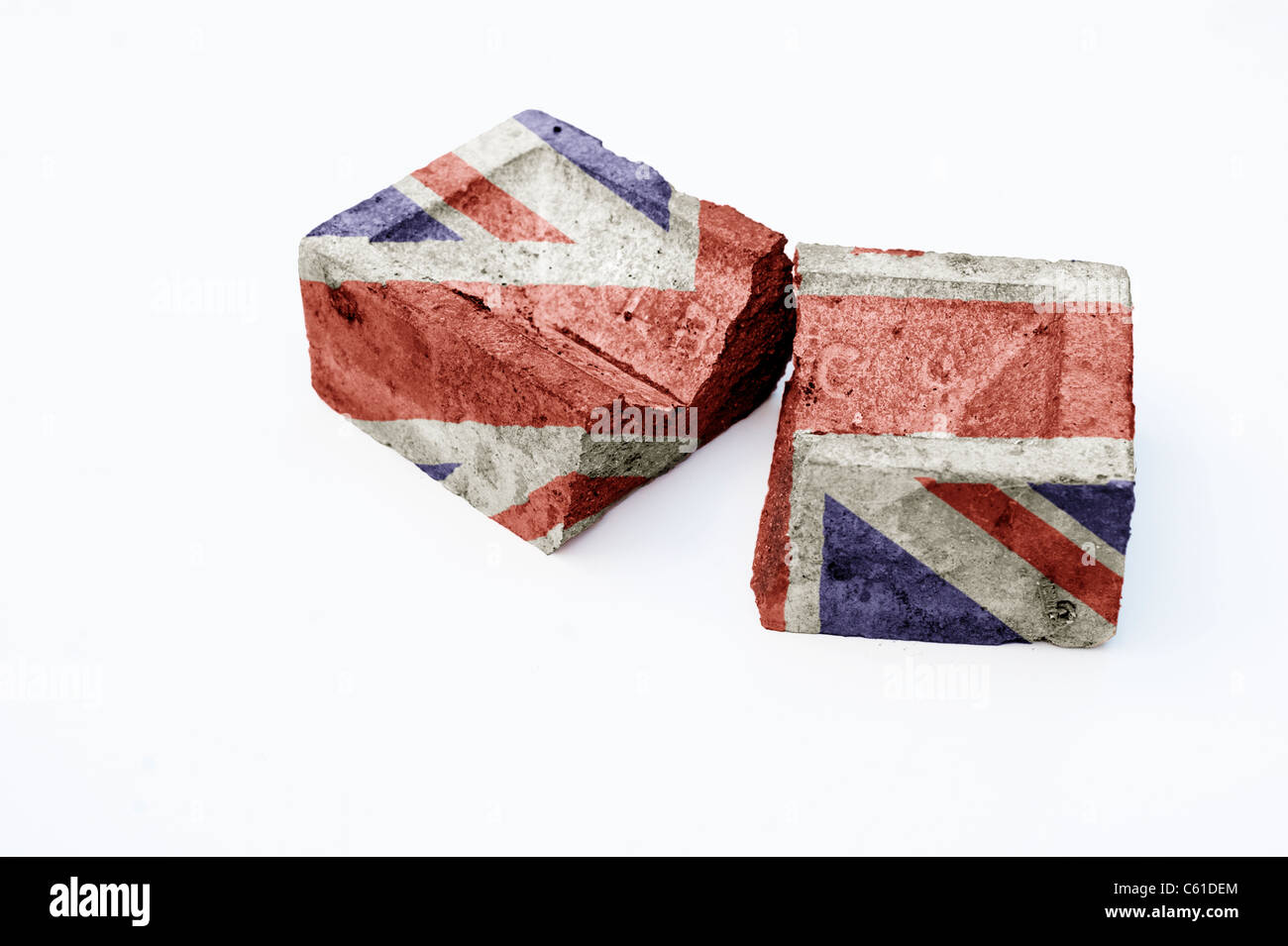 Union Jack on a broken brick on white background . Concept representing the foundation of a broken society - Stock Image