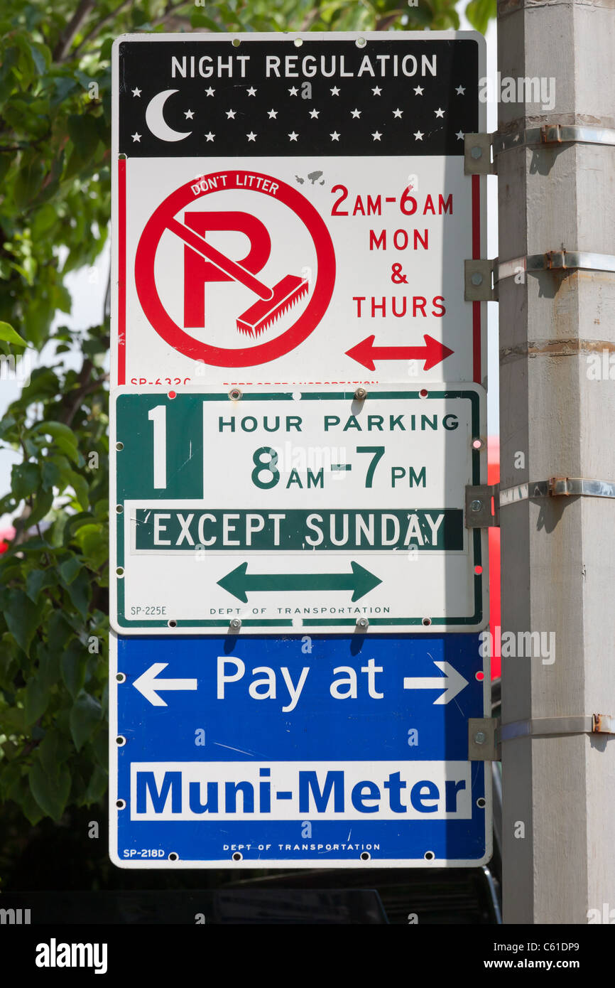 Multiple signs indicate the various parking regulations in-force on a street in New York City. - Stock Image