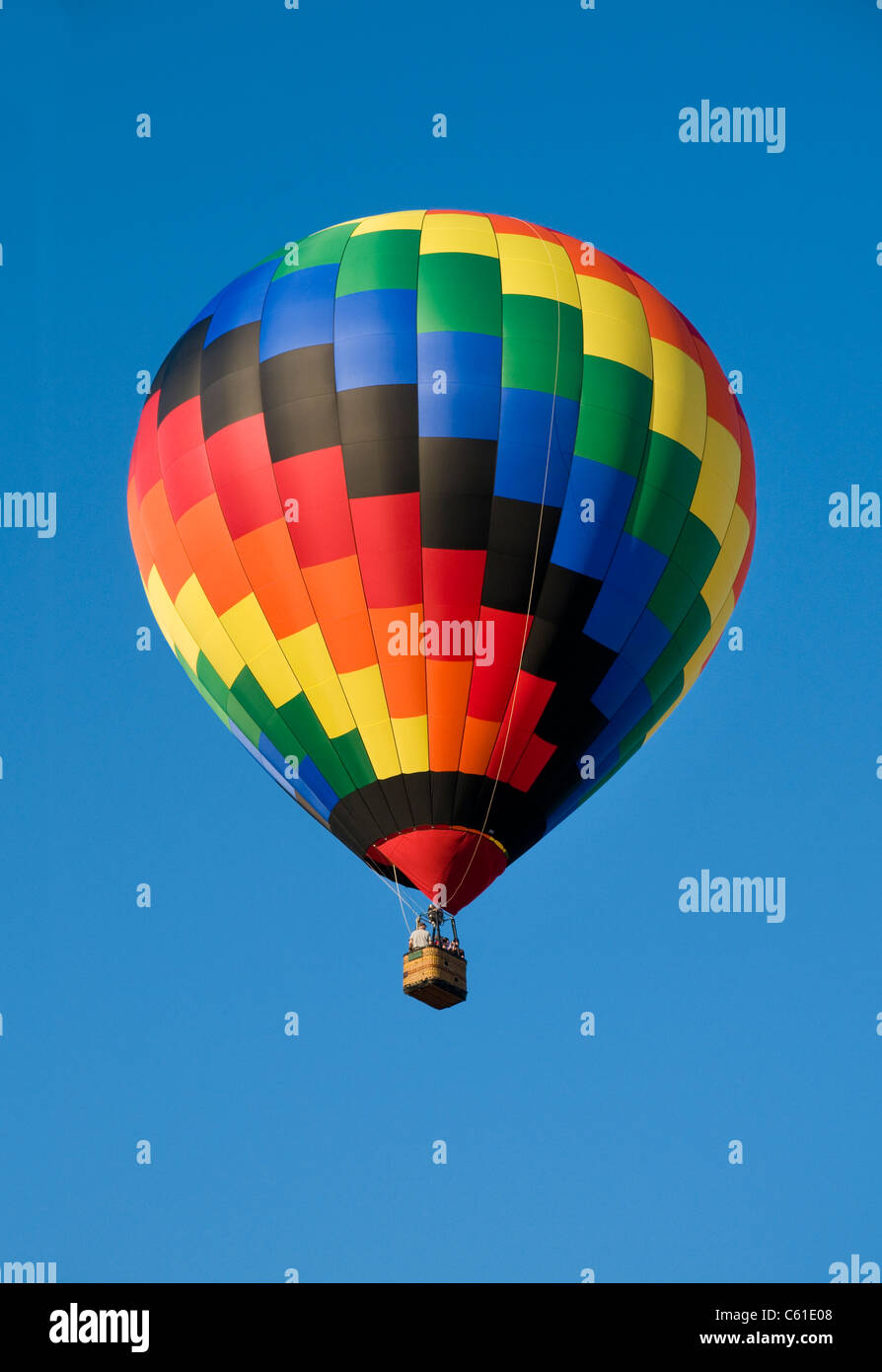 Colorful hot-air balloon floating against blue sky - Stock Image