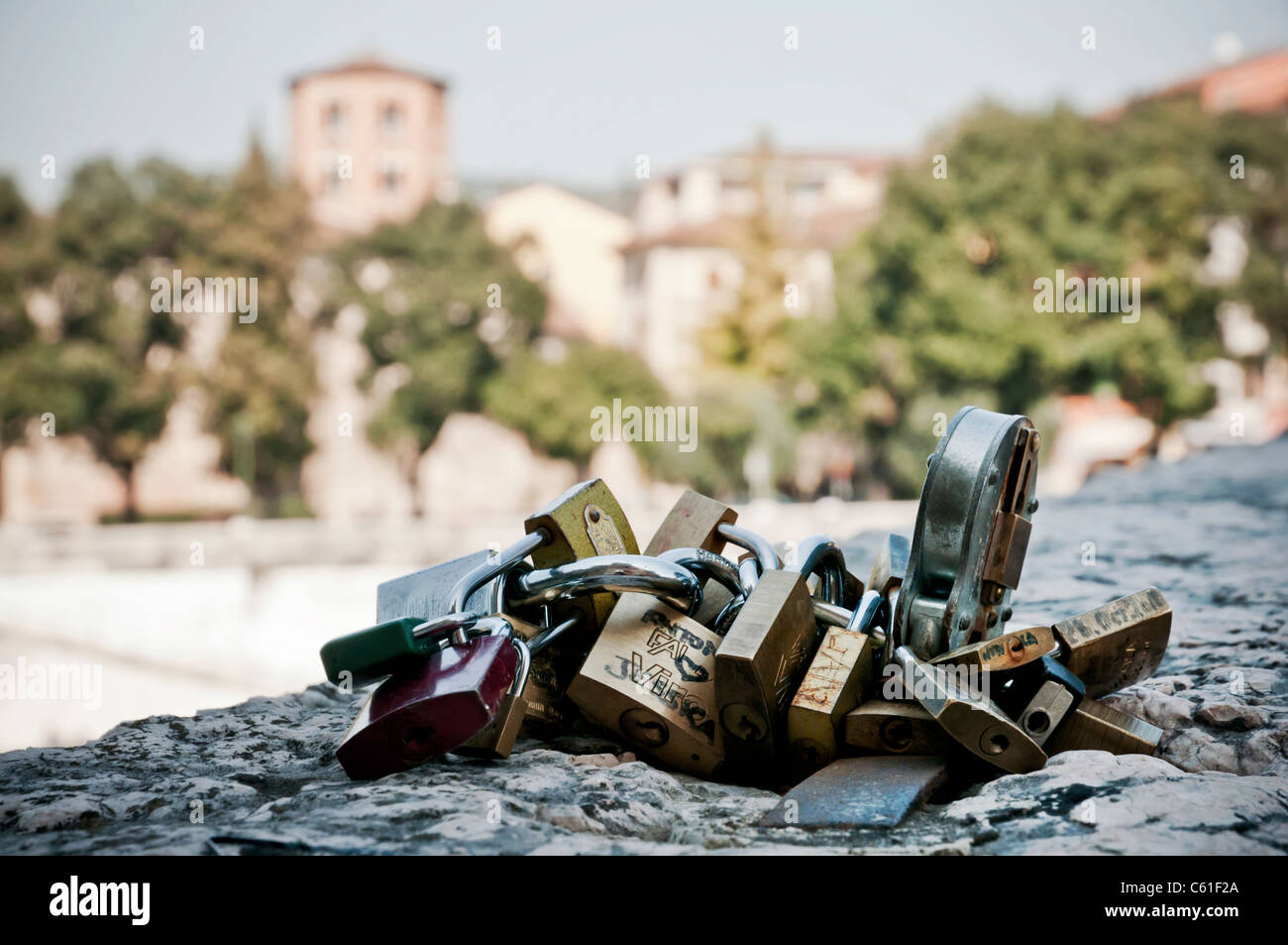 Love Padlocks tied to stone bridge, Verona Italy - Stock Image