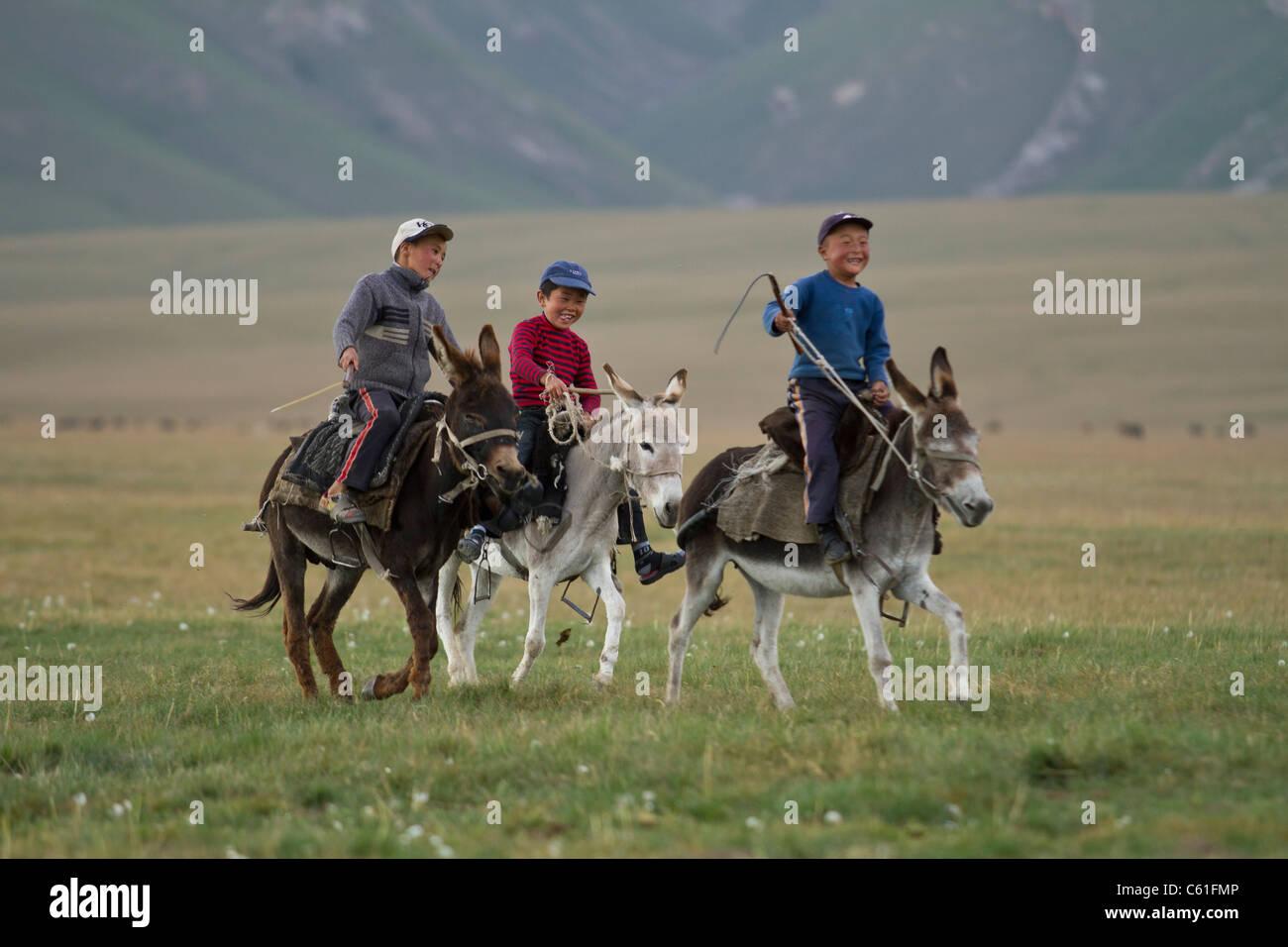 Three children riding on a donkeys, Kyrgyzstan - Stock Image