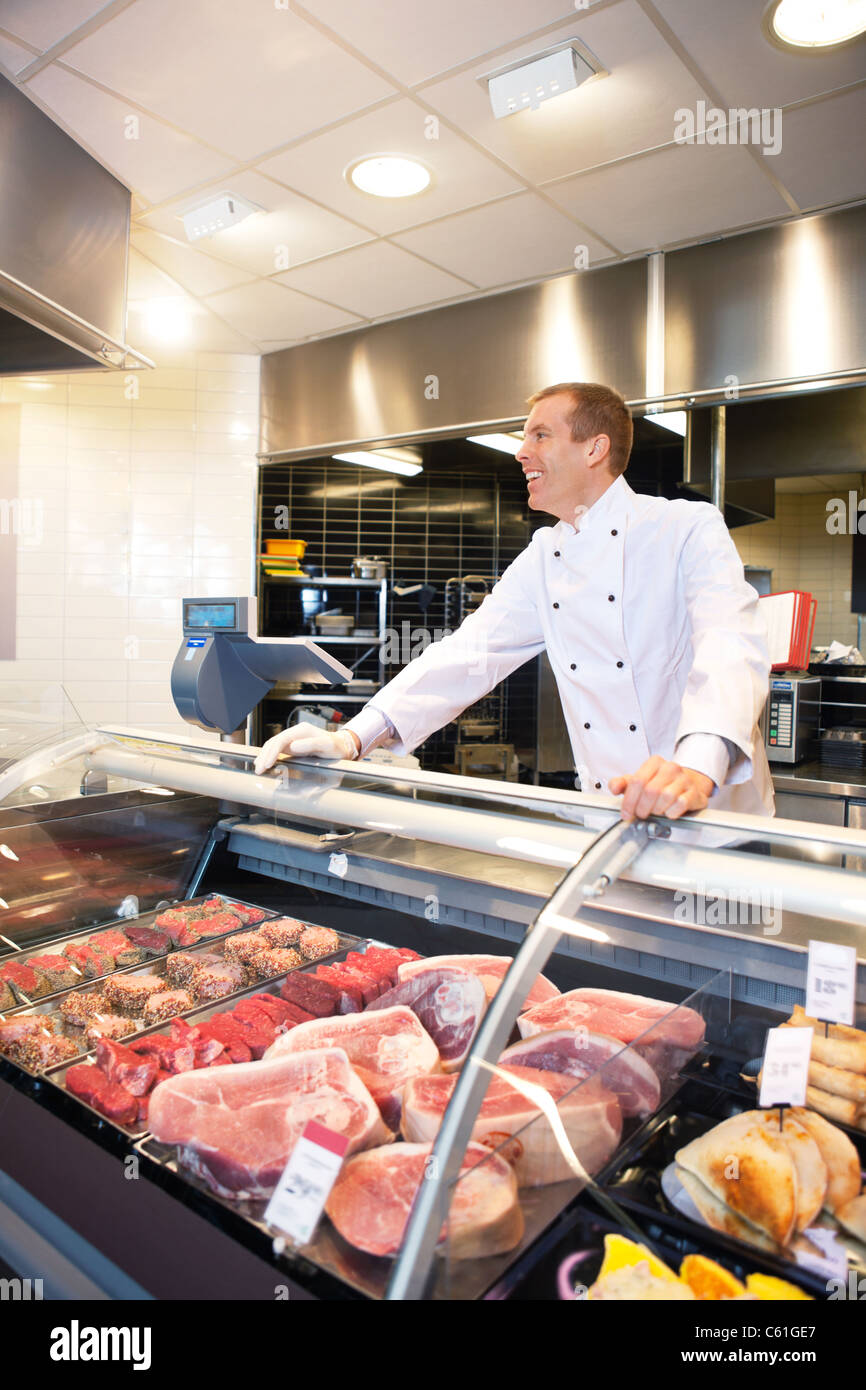 Cheerful chef on the counter of frozen meat in the supermarket - Stock Image
