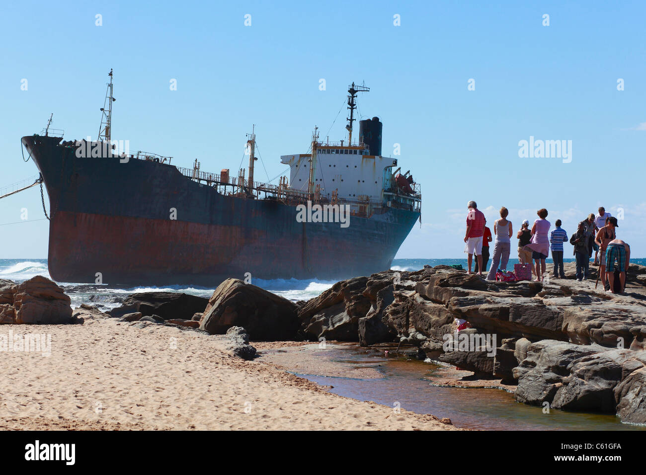 Interested onlookers gaze at the tanker Phoenix, aground on a rocky shelf at Sheffield Beach, KwaZulu Natal, South - Stock Image