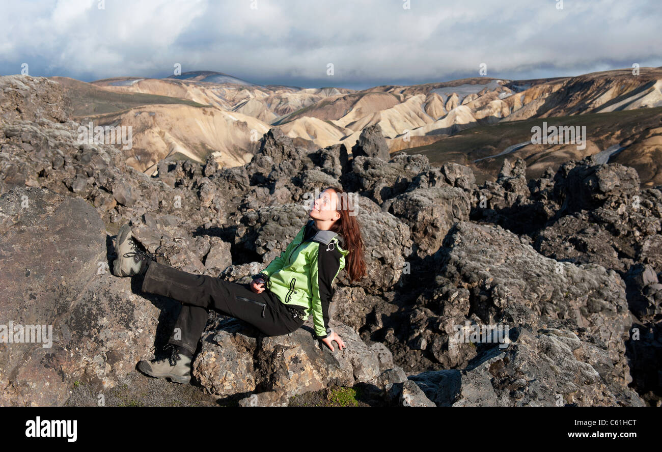 young women tourist sunbathing on the lava field at Landmannalaugar, Iceland - Stock Image