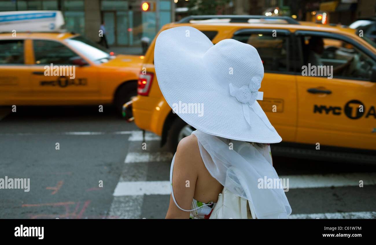 A woman wearing a big, floppy, white hat waits to cross the street in the New York neighborhood of Chelsea - Stock Image
