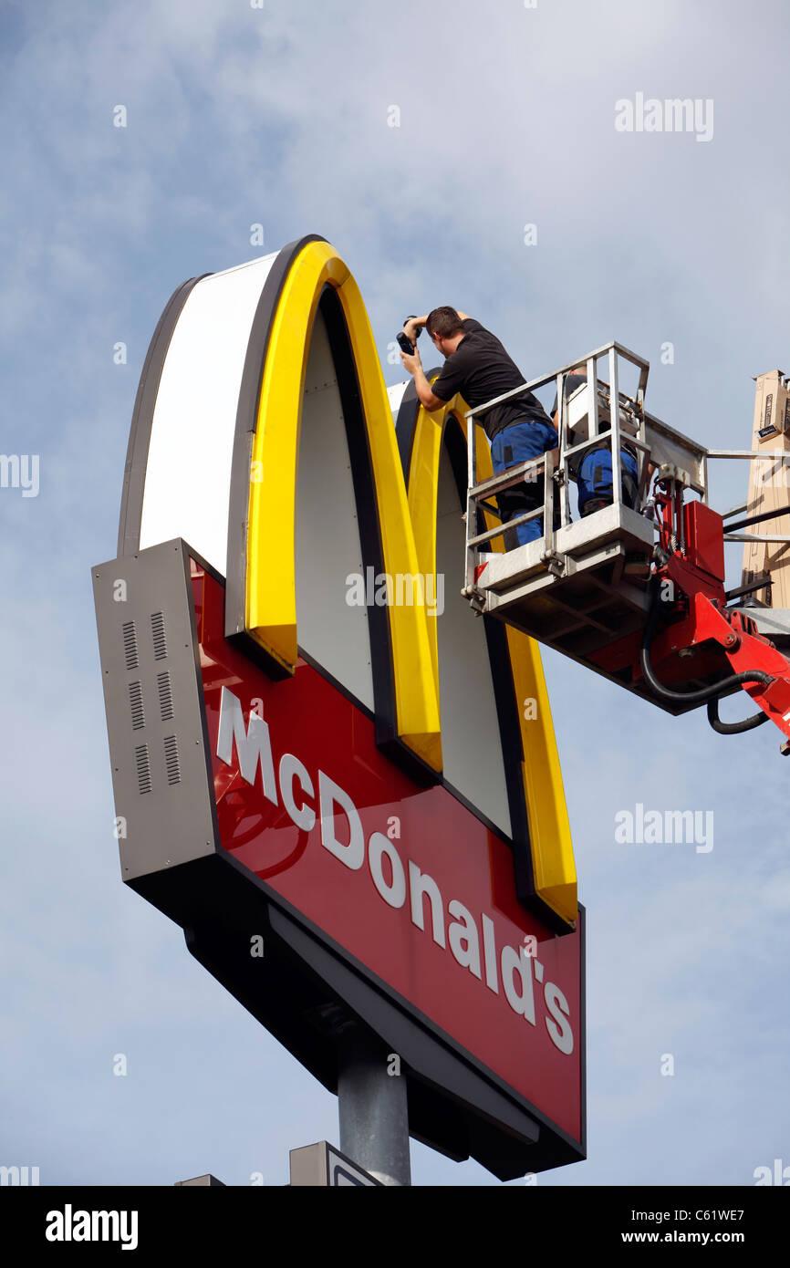 Repair of a McDonald's Restaurant neon sign. - Stock Image
