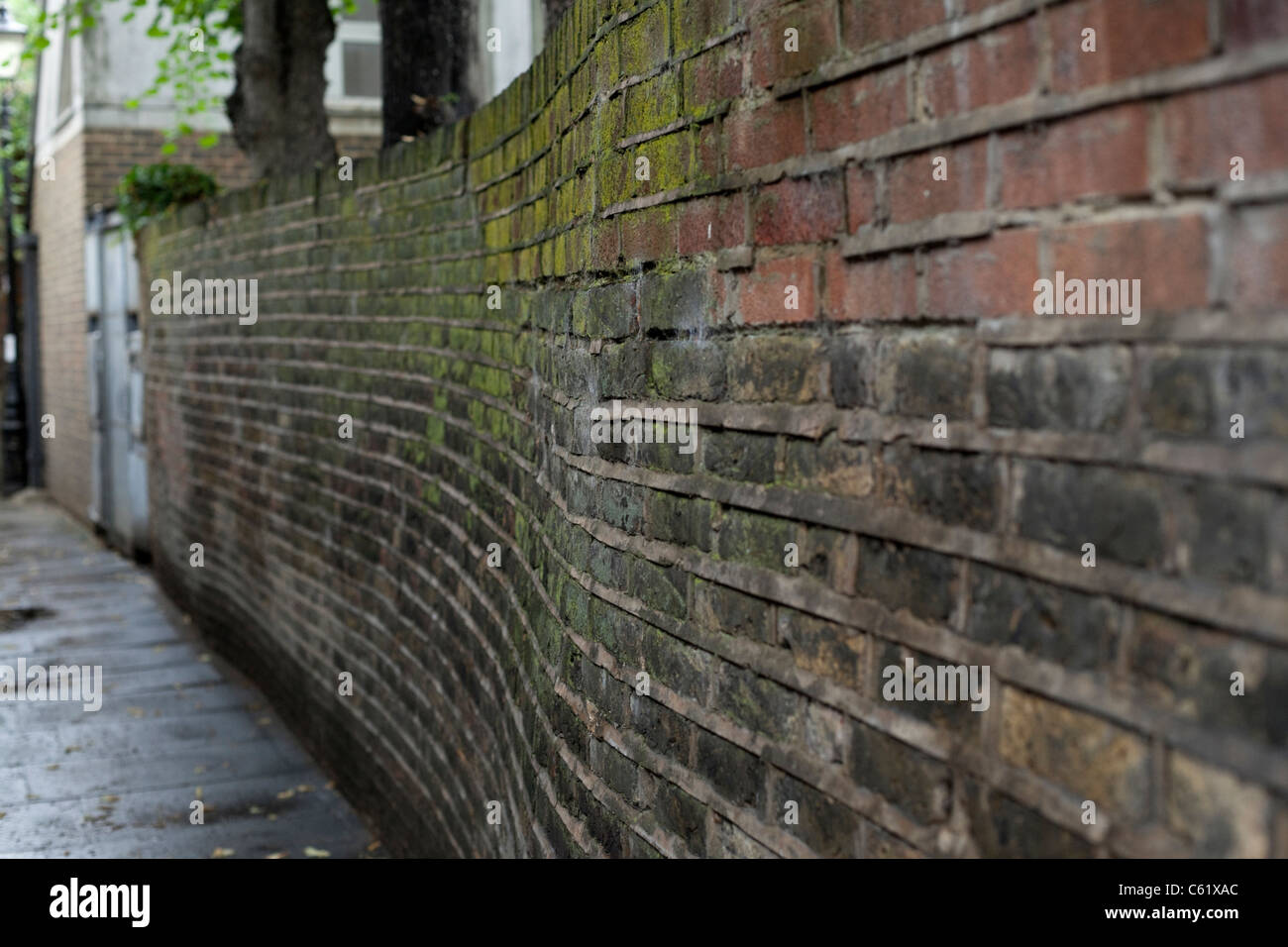Crooked brick wall, London, England, UK. - Stock Image