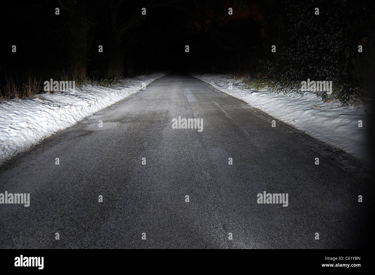 Snowy car lit road - Stock Image