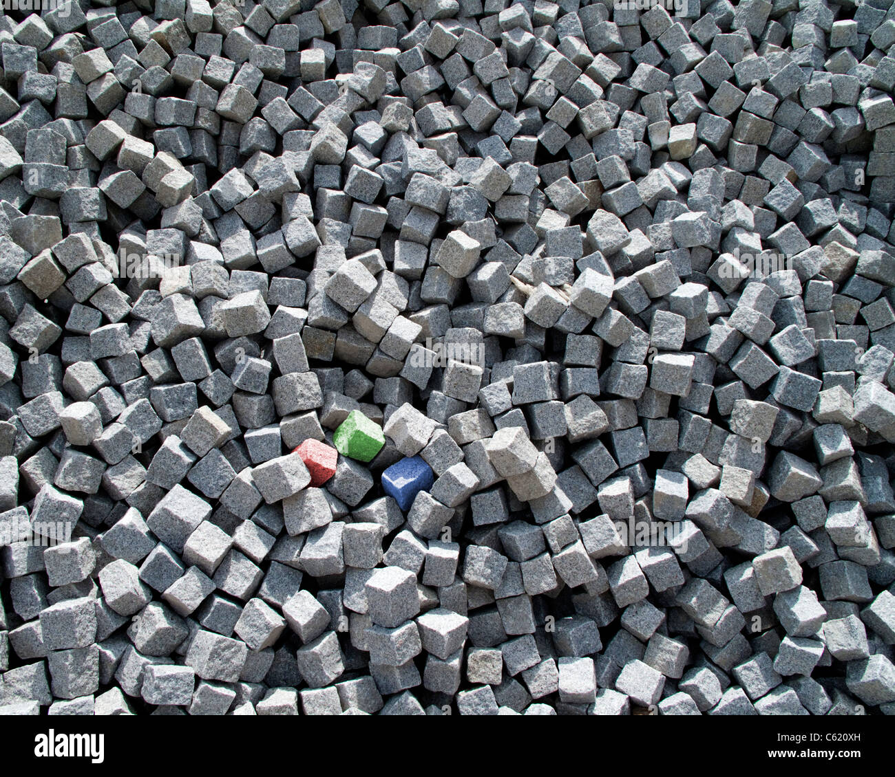 RGB CONCEPT: Three coloured granite cubes (red, green & blue) amongst a collection of grey granite sets. - Stock Image