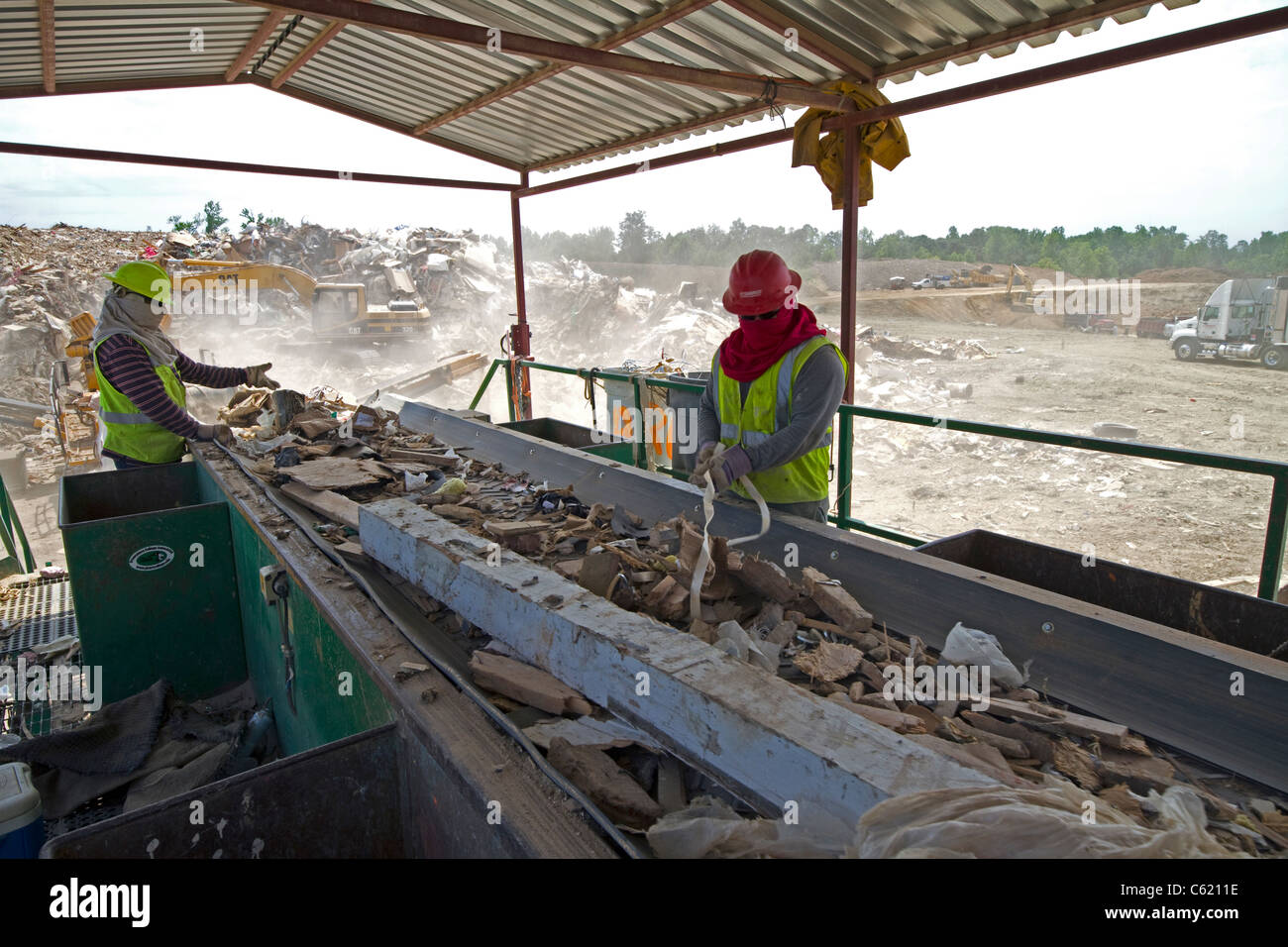 Workers sorting recyclables at landfill - Stock Image
