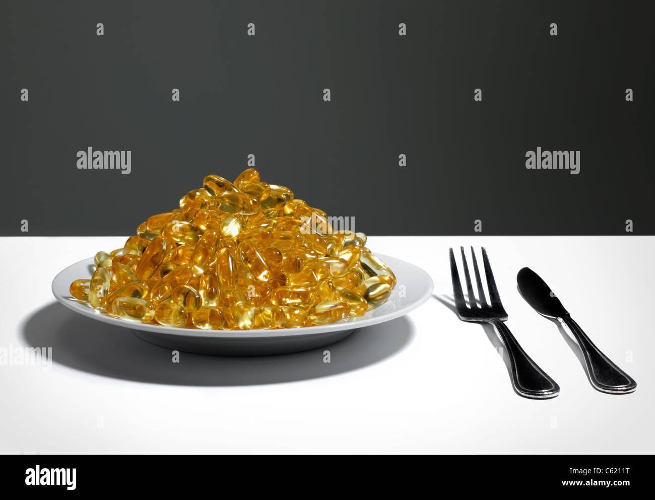 Plate of full of Vitamin E or Fish oil capsules - Stock Image