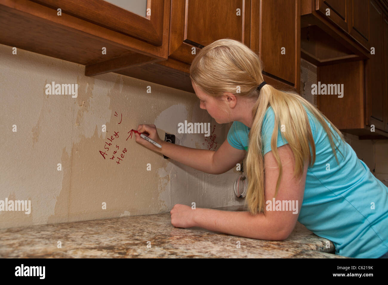 Teen girl writing on unfinished areas of kitchen remodel. MR Myrleen Pearson - Stock Image