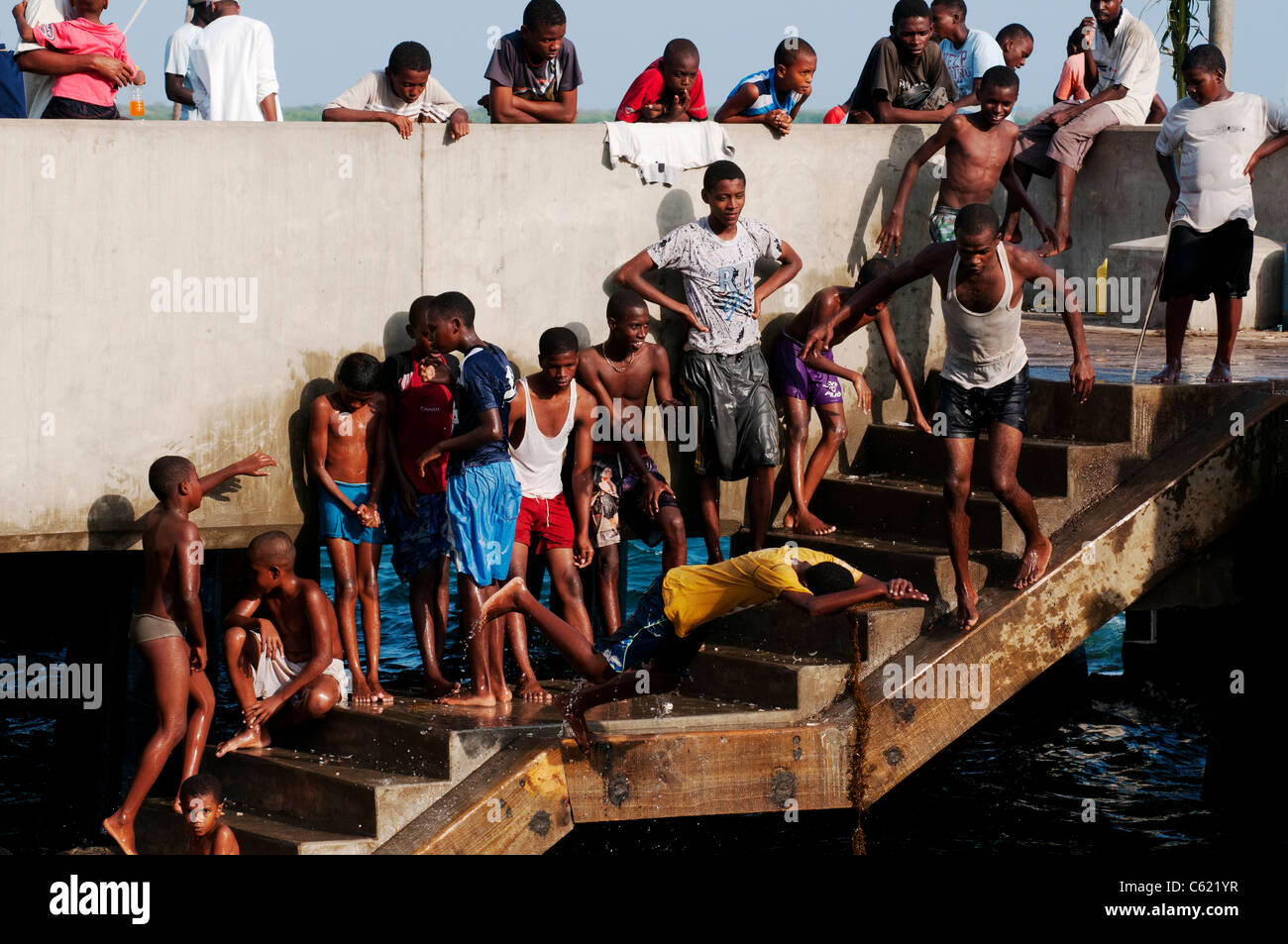 African youth playing on Lamu jetty Stock Photo