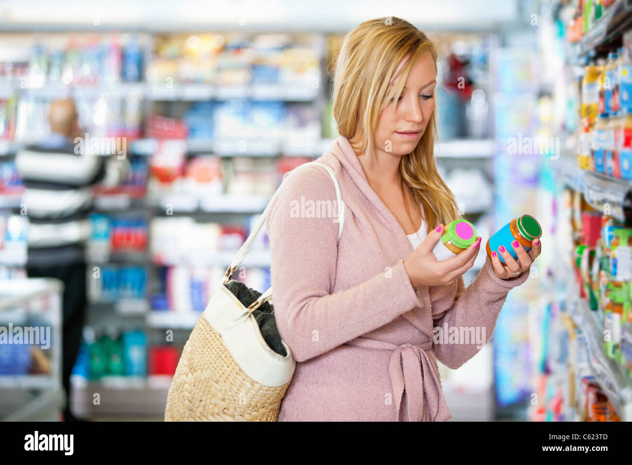 Young woman holding jar in the supermarket with people in the background - Stock Image
